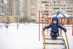 逗人喜爱的小孩男孩在五颜六色的冬天给放下穿衣  与孩子的户外激活休闲 愉快的子项 免版税图库摄影
