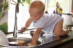 逗人喜爱的小孩男孩洗涤的盘在国内厨房里 使用与水龙头的可爱的男婴 免版税库存图片