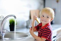 逗人喜爱的小孩男孩洗涤的盘在国内厨房里 库存照片