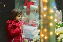 逗人喜爱的小孩,男孩,与玩具的观看的圣诞节装饰 库存图片