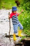 逗人喜爱的小孩,男孩,使用在一个小的池塘,飞溅wate 免版税库存照片