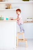逗人喜爱的小孩婴孩在台阶凳子上升,设法到达在高书桌上的事在厨房 图库摄影