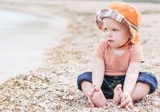 逗人喜爱的小孩婴孩坐海滩 库存图片