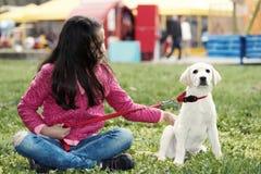 逗人喜爱的小狗青春期前的女孩公园开会 库存照片