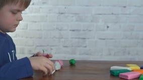 逗人喜爱的小男孩从在桌上的彩色塑泥铸造 股票录像