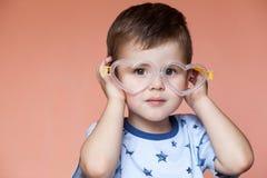 逗人喜爱的小男孩佩带的心形的玻璃画象  免版税图库摄影