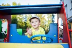 逗人喜爱的小男孩充当一辆大玩具木汽车 免版税库存图片