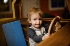 逗人喜爱的小男孩充当玩具木汽车 库存照片