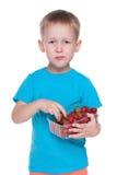 逗人喜爱的小男孩吃草莓 免版税库存照片