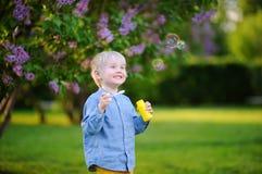 逗人喜爱的小男孩吹的肥皂泡在美丽的夏天公园 免版税库存图片