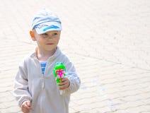 逗人喜爱的小男孩吹的肥皂泡 免版税库存图片