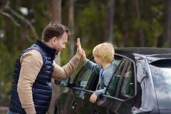 逗人喜爱的小男孩和他的父亲准备好旅行或旅途乘汽车 他们表达他们的与一个高的五姿态的欢欣 免版税库存照片