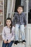 逗人喜爱的小男孩和姐妹坐楼梯 免版税库存图片