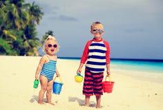 逗人喜爱的小男孩和小孩女孩使用与沙子 免版税库存照片
