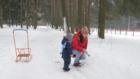 逗人喜爱的小男孩和年轻母亲在与雪的冬天使用在公园 蓝色孩子` s夹克和红色在妈妈 股票录像