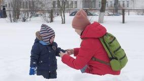 逗人喜爱的小男孩和年轻母亲在与雪的冬天使用在公园 蓝色孩子` s夹克和红色在妈妈 股票视频