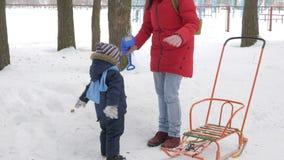 逗人喜爱的小男孩和年轻母亲在与雪的冬天使用在公园 蓝色孩子` s夹克和红色在妈妈 影视素材