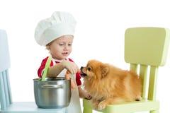 逗人喜爱的小男孩和滑稽的狗在家 免版税库存图片