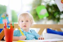逗人喜爱的小男孩图画和绘画与五颜六色的记号笔在幼儿园 免版税库存照片