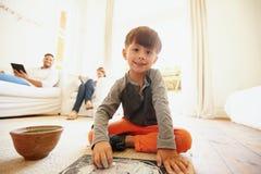 逗人喜爱的小男孩图画和着色在客厅 免版税库存照片
