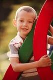 逗人喜爱的小男孩在一个五颜六色的孩子操场 免版税库存照片