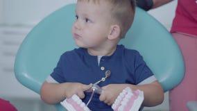 逗人喜爱的小男孩在使用与下颌嘲笑的牙医办公室在女性医生和护士帮助下  无忧无虑的孩子 影视素材