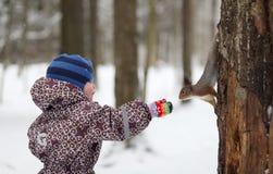逗人喜爱的小男孩在冬天森林喂养一只灰鼠 免版税库存照片