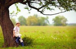 逗人喜爱的小男孩在大开花的洋梨树下,乡下 免版税库存照片
