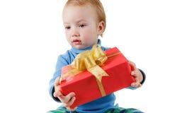 逗人喜爱的小男孩在白色打开礼物盒并且高兴,隔绝 库存照片