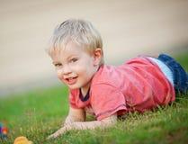逗人喜爱的小男孩在草说谎户外并且对凸轮微笑 图库摄影