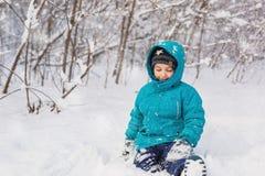 逗人喜爱的小男孩在雪坐在公园在冬天 库存照片