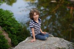 逗人喜爱的小男孩坐一个小湖的岸 库存照片