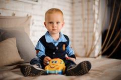 逗人喜爱的小男孩坐与一个玩具的床在他的手上 免版税图库摄影
