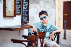 逗人喜爱的小男孩坐在室外咖啡馆的一把椅子 免版税库存图片