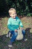 年轻逗人喜爱的小男孩坐玩具母牛外面 免版税库存照片