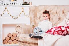 逗人喜爱的小男孩坐长沙发并且看在惊奇的照相机 一个人有时髦的易洛魁族的理发的和时髦的 库存图片