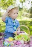 逗人喜爱的小男孩外部举行的复活节彩蛋打翻他的帽子 免版税库存照片