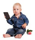 逗人喜爱的小男孩开会拿着手机,被隔绝的玫瑰 免版税库存照片