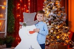 逗人喜爱的小男孩开头礼物盒在红色房子内部的圣诞树下 免版税库存图片