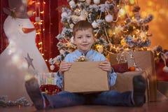 逗人喜爱的小男孩开头礼物盒在红色房子内部的圣诞树下 库存照片