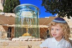 逗人喜爱的小男孩站立在金黄犹太教灯台 库存照片