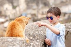 逗人喜爱的小男孩遇见了一只猫,当走在典型的意大利镇时 库存照片