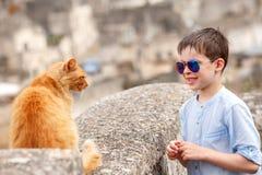 逗人喜爱的小男孩遇见了一只猫,当走在典型的意大利镇时 免版税库存图片