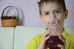 逗人喜爱的小男孩饮用的汁液在家,樱桃汁从一个瓶或一块玻璃喝与秸杆 库存照片