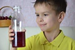 逗人喜爱的小男孩饮用的汁液在家,樱桃汁从一个瓶或一块玻璃喝与秸杆 图库摄影