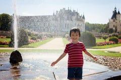 逗人喜爱的小男孩,使用在一座城堡前面的雨中在Fra 库存照片