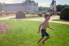 逗人喜爱的小男孩,使用在一座城堡前面的雨中在Fra 库存图片