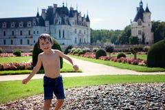 逗人喜爱的小男孩,使用在一座城堡前面的雨中在Fra 免版税库存图片
