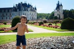 逗人喜爱的小男孩,使用在一座城堡前面的雨中在Fra 免版税库存照片