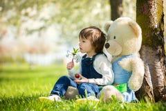 逗人喜爱的小男孩,吃草莓在晴朗的春天的公园 免版税图库摄影